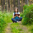 Young woman levitating with the book - Stock Photo