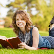 Stock Photo: Charming girl lies on green grass and reads book
