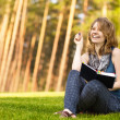 Stock Photo: Young woman sitting on green grass and reads book