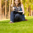 Stockfoto: Young beautiful womon green summer meadow reads textbook.