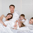 Happy family with kids on white bed in the bedroom - Stock Photo