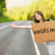 Stock Photo: Pretty young woman tourist hitchhiking along a road.