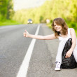 Pretty young woman hitchhiking along a road. — Stock Photo