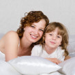 Royalty-Free Stock Photo: Young mother and her daughter lying in bed