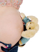 Pregnant girl showing her belly and holding a toy. — Foto de Stock