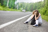 The sad girl hitchhiking along a road. — Stock Photo