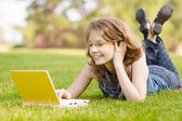 College student lying down on the grass working on laptop at campus — Stock Photo
