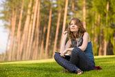 Mladá krásná žena sedící na zelené trávě a čte knihu — Stock fotografie