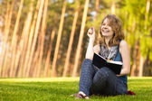 Young woman sitting on green grass and reads book — Photo
