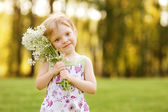 Cute little girl with flowers in sunshine — Stock Photo