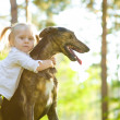 Little girl in the park with a dog — Stock Photo