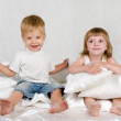 The brother and the sister sit on a bed — Stock Photo