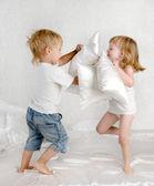Feliz risa hermano y hermana teniendo una almohada pelean en la cama en su casa — Foto de Stock