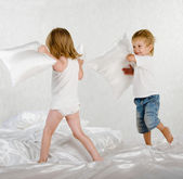 Happy laughing brother and sister having a pillow fight in bed at home — Stock Photo