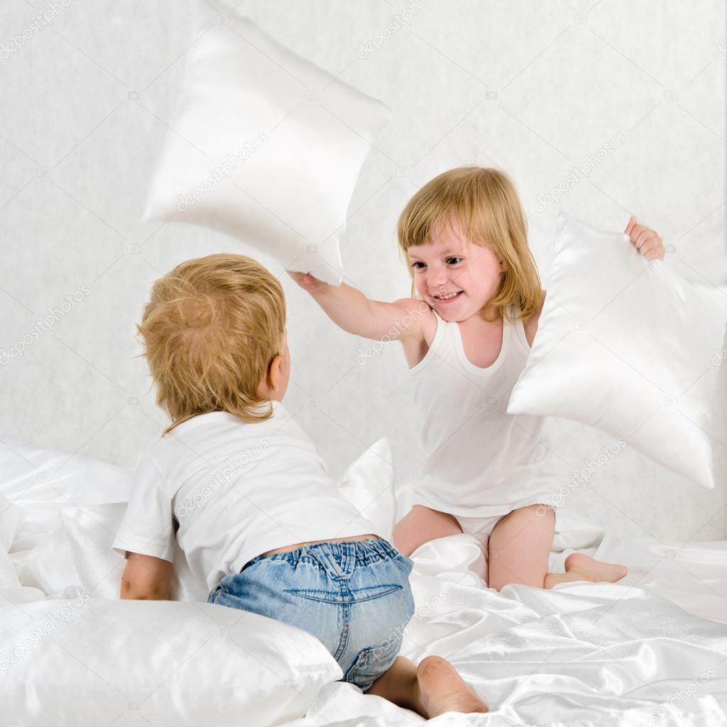 Happy laughing brother and sister having a pillow fight in bed at home  Stock Photo #13826971