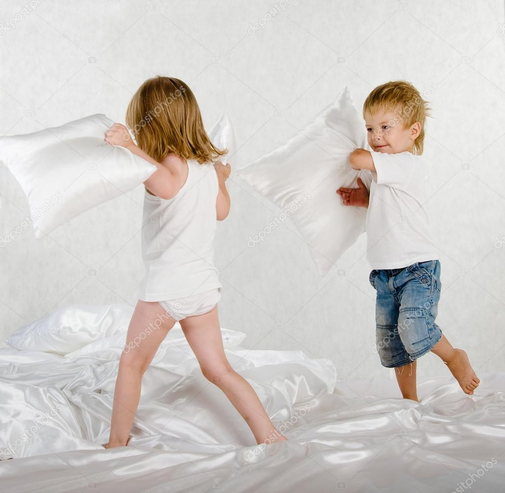 Happy laughing brother and sister having a pillow fight in bed at home — Stock Photo #13826988