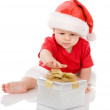 Stock Photo: Baby boy in Santa hat with a gift.