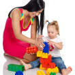 Happy Mother with Daughter playing with blocks — Stock Photo #13833739