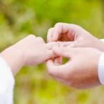 Mans mano mettendo un anello nuziale al dito di spose — Foto Stock