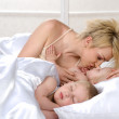 Happy family sleeping together on bed at home — Stock Photo