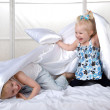 Happy kids having fun with pillows on bed — Stock Photo