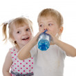 Boy drinks water from a bottle. girl snading by him isolated on white background — Stock Photo