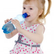 Baby girl drinks water from a bottle. isolated on white background — Stock Photo