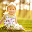 The nice little girl with flowers on the grass in summertime - Foto Stock