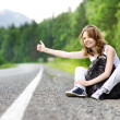 Young smiling woman with backpack catching a car on empty road — Stock Photo