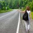 Girl with backpack stops the car on road — Stock Photo #13836468