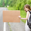 Stock Photo: Young girl hitchhiking with cardboard