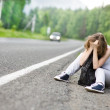Stock Photo: Sad girl hitchhiking along road.