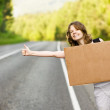 Beautiful young girl hitchhiking with cardboard — Stock Photo #13836630