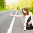 Girl with backpack stops the car on road — Stock Photo #13836791