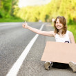 Beautiful young girl hitchhiking with cardboard — Stock Photo #13836813