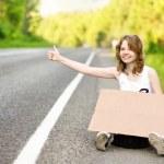 Beautiful young girl hitchhiking with cardboard — Stock Photo