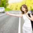 Stock Photo: Girl with backpack stops the car on road