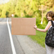 Beautiful young girl hitchhiking with cardboard — Stock Photo
