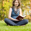 Young woman with book on green grass at park — Stock Photo #13837130