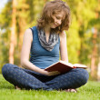 Young woman with book on green grass at park — Stock Photo #13837146