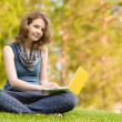 Young woman with laptop sitting on green grass — Stock Photo #13837205