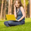 Stock Photo: Young woman with laptop sitting on green grass