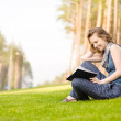 Young woman with book on green grass at park — Stock Photo