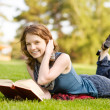 Charming girl lies on green grass and reads book — Stock Photo #13837358