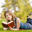 Charming girl lies on green grass and reads book — Stock Photo #13837373