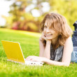 Royalty-Free Stock Photo: College student lying down on the grass working on laptop at campus