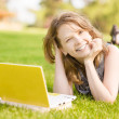 College student lying down on the grass working on laptop at campus — Stock Photo #13837514