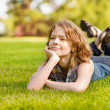 Stock Photo: Young nice attentive woman lies on green grass
