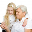 Young smiling granddaughter showing and teaching a mobile phone to her grandmother. isolated on white background — Stock Photo