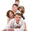 Happy family with kids on white bed in the bedroom — Stockfoto